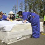 """Ashley Vaudrin and Kelly Selby of the Holiday Inn Express """"Team Sorano"""" rush to make a bed while handcuffed together in Monday's 9th annual Housekeepers Olympics held at Fortune Bay."""