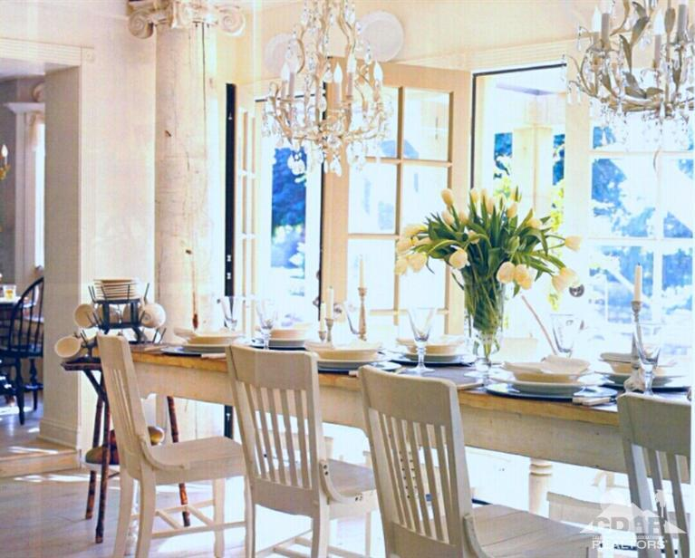Large farm table that's lit by a wall of French doors during the day and chandeliers by night.